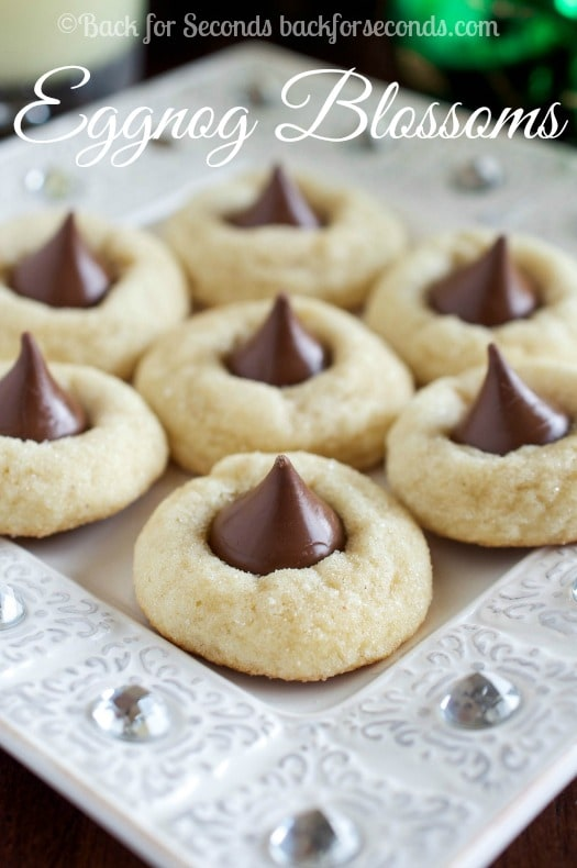 These Eggnog Blossoms are a festive twist on the traditional peanut butter blossoms. Soft, chewy eggnog cookies are rolled in sugar and topped with a kiss!