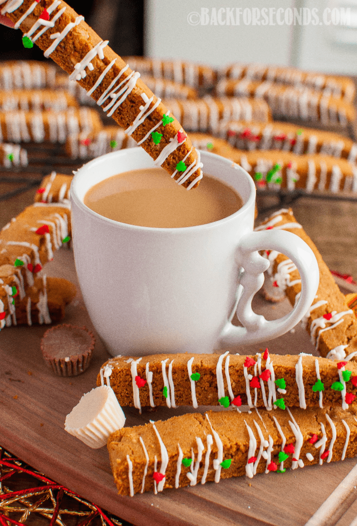 This White Chocolate Peanut Butter Cup Biscotti is perfect with a cup of coffee or milk! A beautiful gift idea for Christmas that's surprisingly easy to make! #christmascookie #peanutbuttercups #whitechocolatepeanutbutter #biscotti #christmas