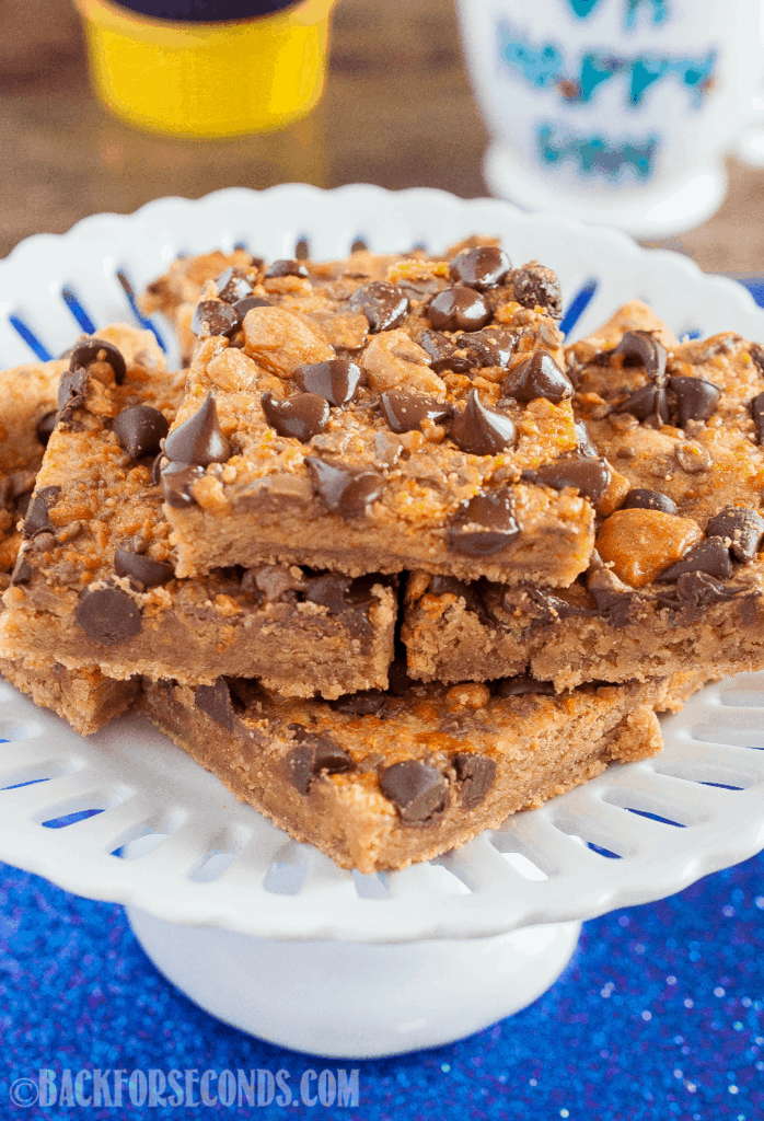Peanut Butter Butterfinger Bars are a rich and chewy, easy dessert recipe! Fudgy, brownie like bars topped with crunchy Butterfinger bits and chocolate chips! #dessert #cookiebars #brownies #peanutbutter #butterfinger