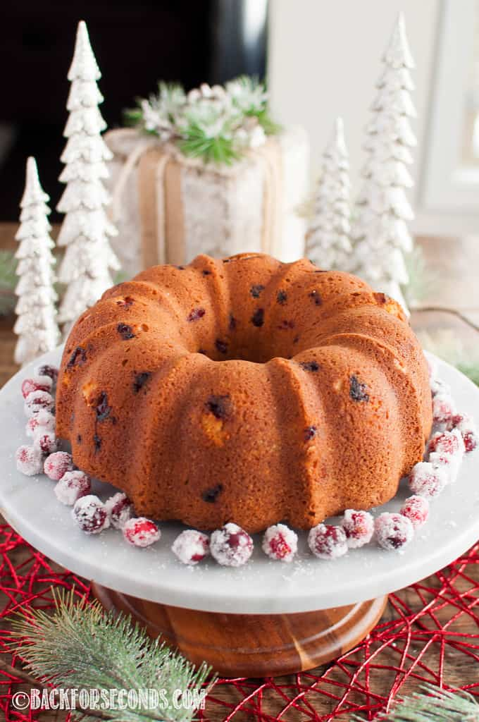 Cranberry Christmas Cake on a cake stand surrounded by sugared cranberries