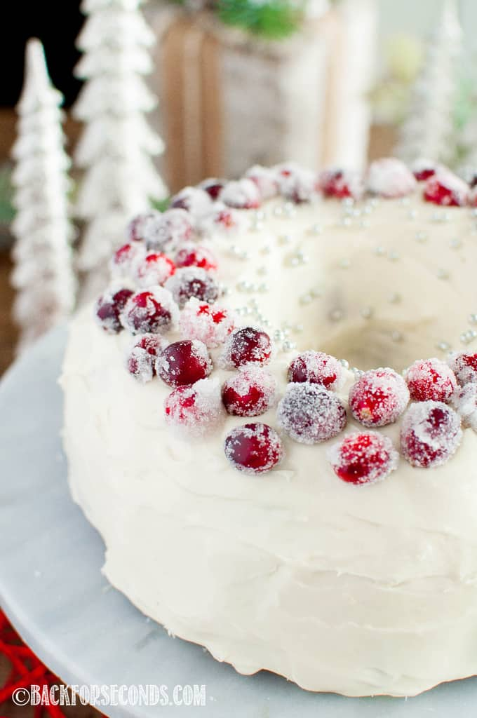 close up shot Cranberry Christmas Cake with Cream Cheese Frosting and sugared cranberries on top