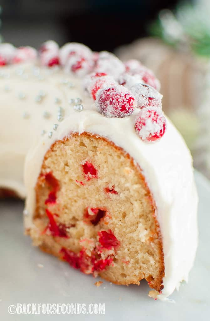 Sliced Cranberry Christmas Cake with Cream Cheese Frosting and sugared cranberries on top